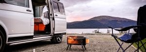 Lifestyle shot of parked campervan beside a lake in the mountains with portable BBQ lit, camp chair and doors open