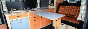 Funky orange and navy tartan bespoke campervan interior with eco birch plywood bespoke storage and kitchen units with clever foldaway table