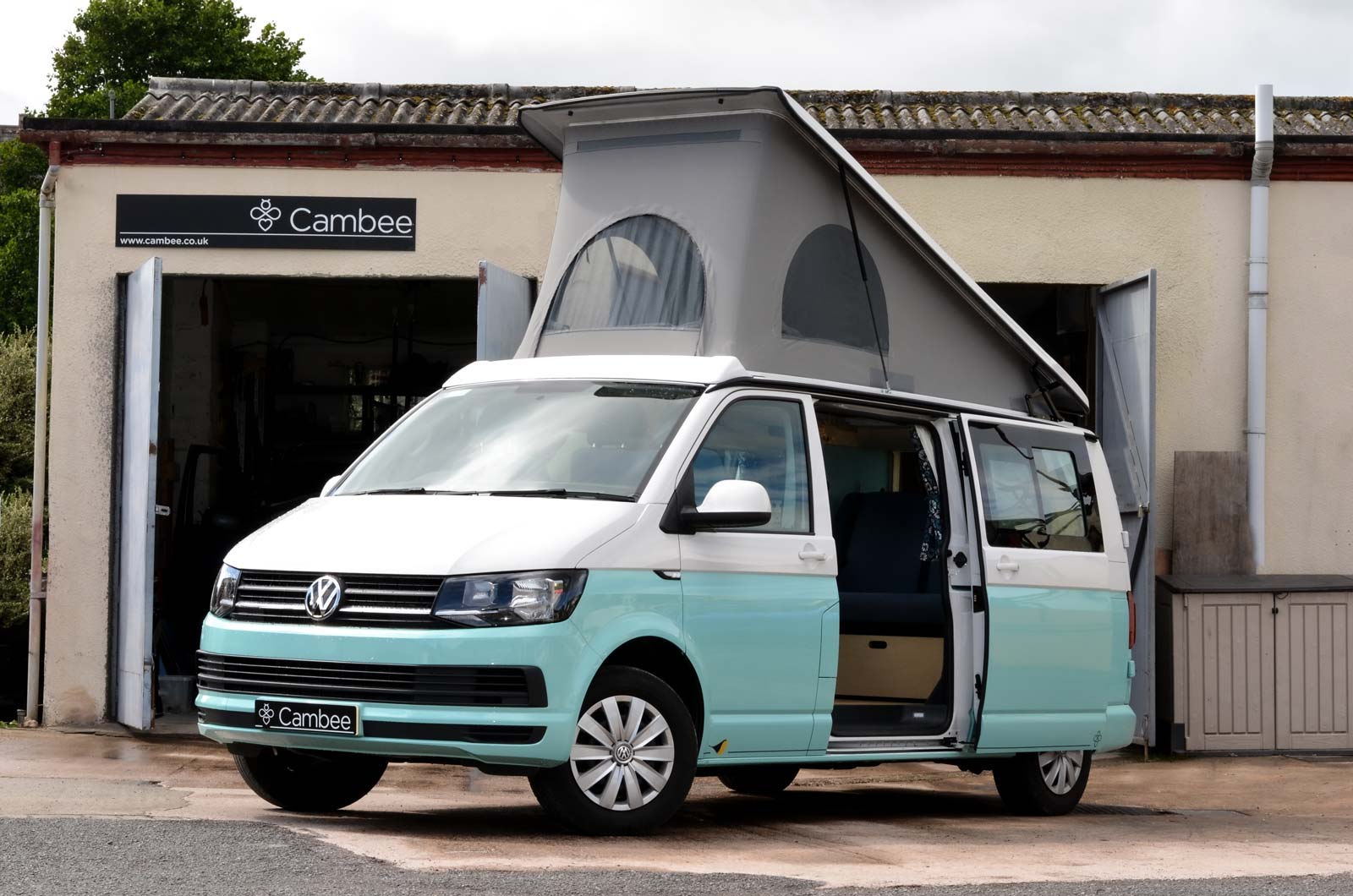 Two tone white and mint cool VW T6 campervan eco conversion with elevated roof parked at Cambee workshop