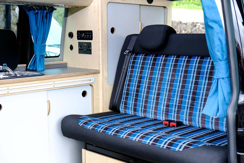 Bespoke white and blue campervan interior eco birch plywood showing blue and white seats and clever storage