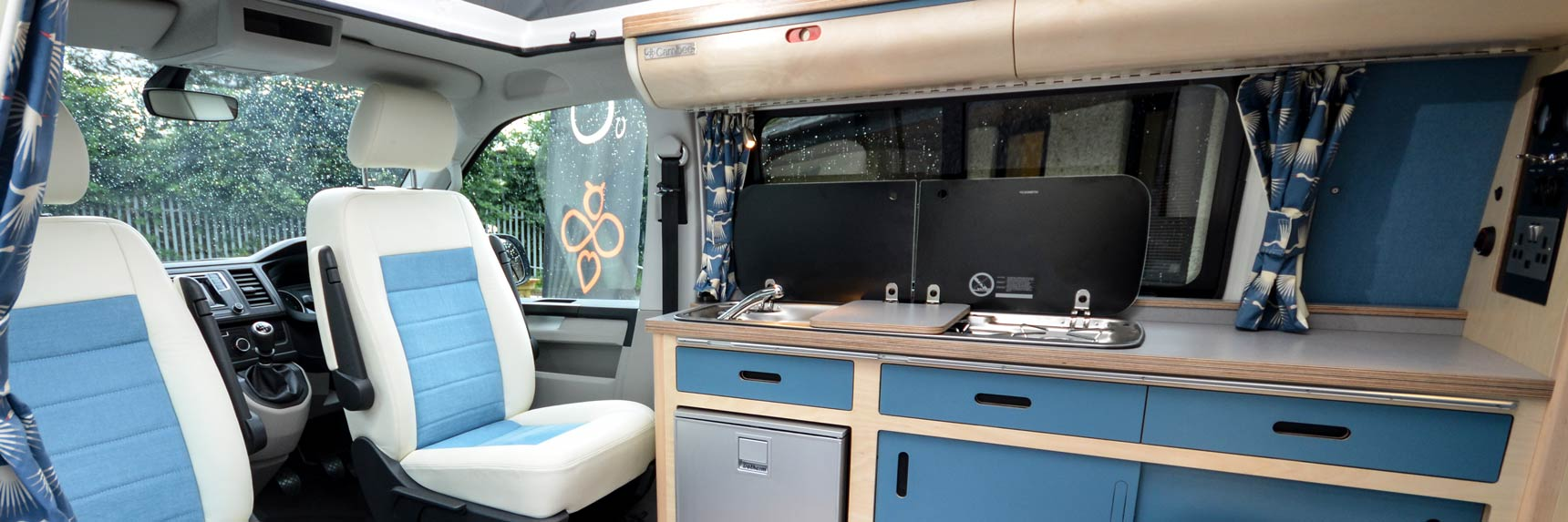 Blue and white cool eco campervan conversion with bespoke birch plywood kitchen, built-in fridge freezer, sink, gas hobs with clever overhead locker storage and smart seating