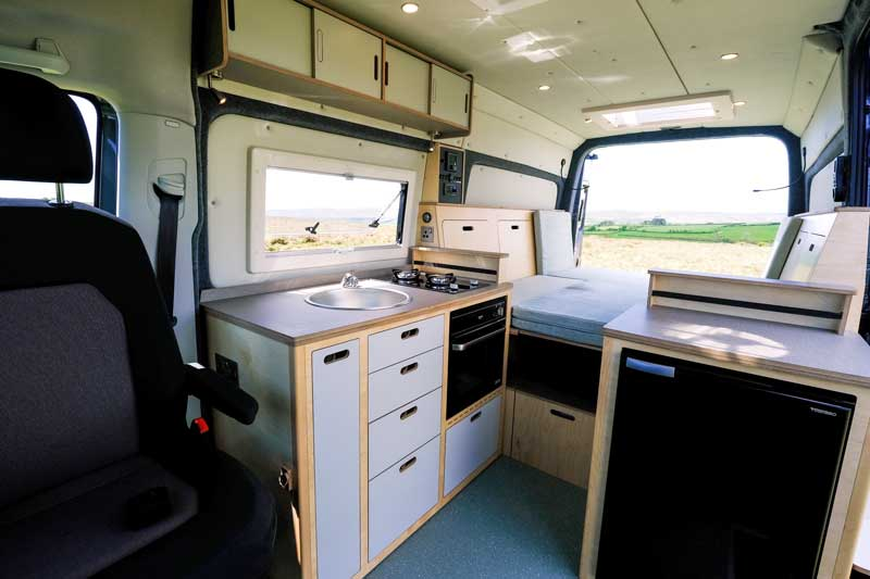 clever bespoke eco birch plywood kitchen unit with sink, double gas hob, clever storage draws and built-in oven in campervan with back door open parked in field with fridge freezer and fold down beds